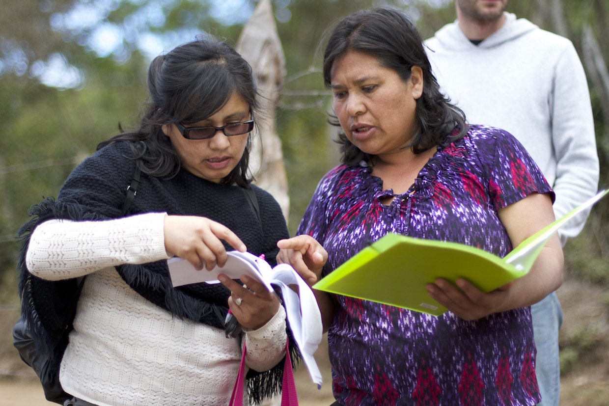 Mayra Orellana-Powell (L) consults with a producer in Santa Elena Honduras